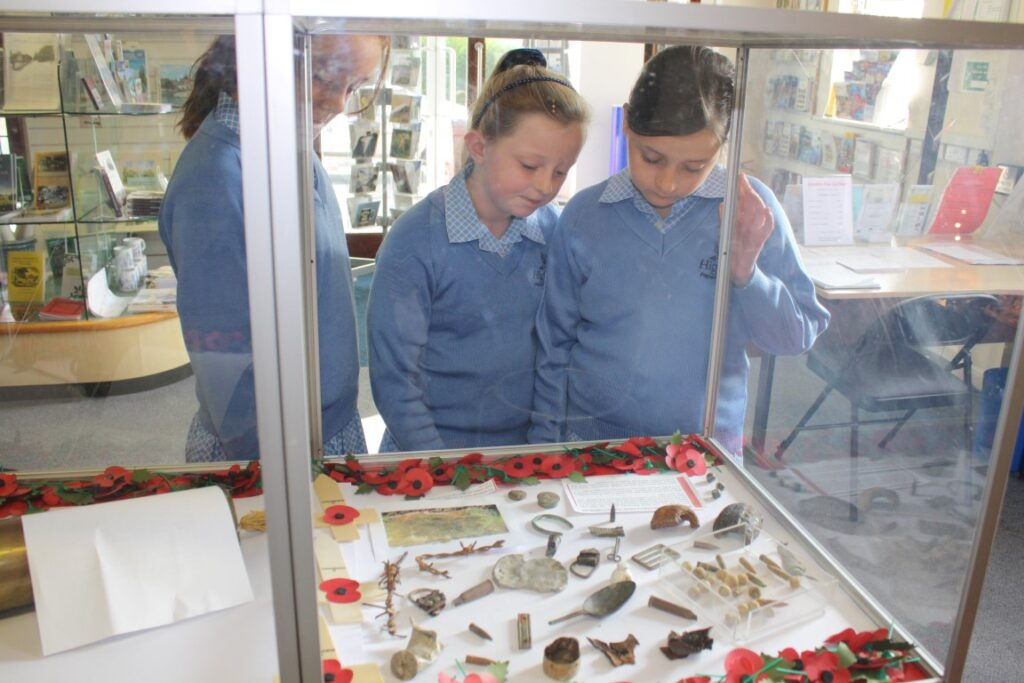 Students examine a display of WW1 battlefield finds.